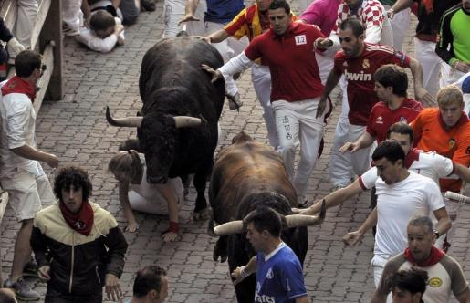 Una chica cae ante los toros de la ganadería madrileña de Victoriano del Río, en el tramo del callejón que da acceso a la plaza de toros de Pamplona durante el sexto encierro de los Sanfermines 2012.