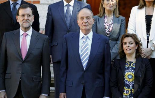 El rey Juan Carlos, junto al presidente del Gobierno, Mariano Rajoy (i), y la vicepresidenta, Soraya Sáenz de Santamaría, posa en la foto de familia, momentos antes de la reunión del Consejo de Ministros que preside hoy en el Palacio de la Zarzuela.