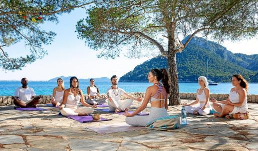 Lucrecia Sarmiento, de espaldas, en una clase de yoga nidra, a primera hora de la mañana en la playa de Formentor, uno de sus rincones favoritos de la Isla.
