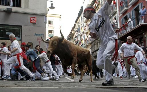 Los toros de la ganadería Torrehandilla-Torreherberos, de Vilches (Jaén), a su llegada a la curva de Mercaderes, durante el octavo y último encierro de los Sanfermines 2012.