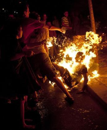 Los protestantes tratan de apagar las llamas de un ciudadano que se ha inmolado durante una protesta en Tel Avivi.
