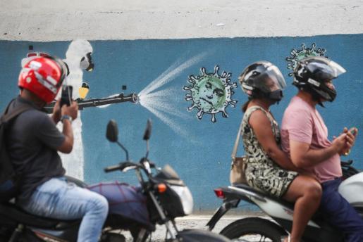 Un hombre fotografía en Brasil un mural sobre el coronavirus.