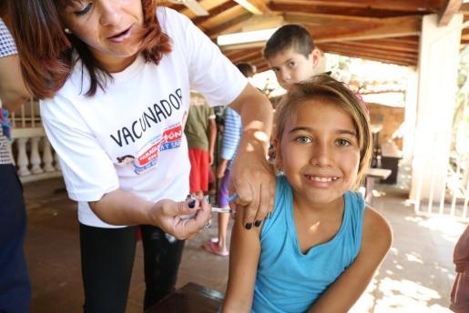 Una sanitaria pone una vacuna a una niña.