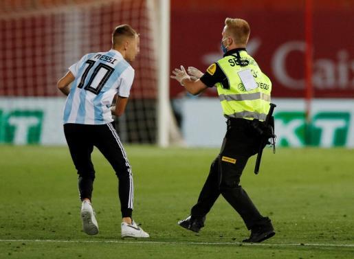 Un miembro del equipo de seguridad trata de abordar al joven en el campo de fútbol del Real Mallorca.