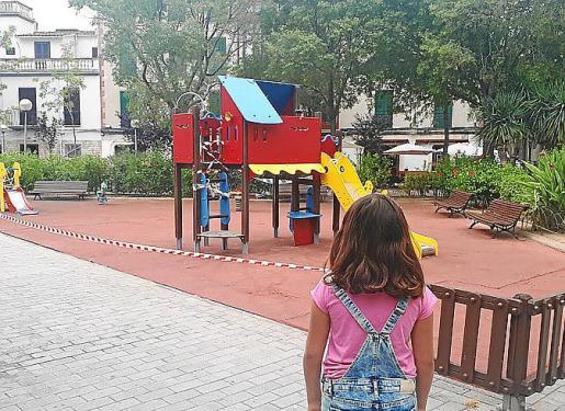 Una niña contempla unos juegos que no puede pisar desde hace más de tres meses.