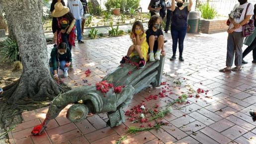 Dos niños se han subido a la estatua de Fray Junípero tras ser derribada.