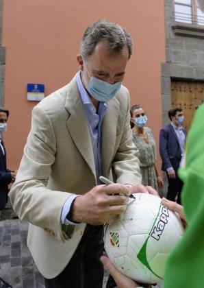El Rey Felipe firma un balón de fútbol a un hombre que le esperaba a las puertas de la Casa Museo de Benito Pérez Galdós en Las Palmas de Gran Canaria.