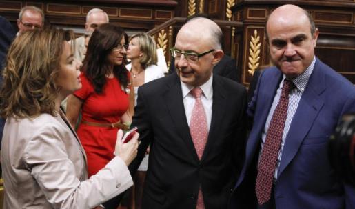 Soraya Sáenz de Santamaria junto a Cristóbal Montoro y Luis de Guindos, esta mañana en el Congreso.