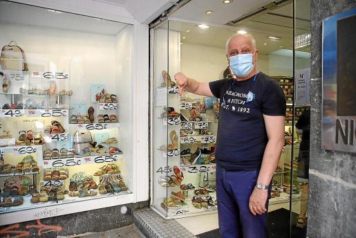 Juan Guardiola, en la puerta de su zapatería, hace un expresivo gesto sobre lo que espera de las rebajas.