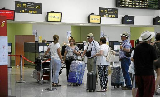 La cancelación de vuelos se encuentra entre las situaciones más frecuentes. Imagen de archivo de pasajeros a punto de embarcar en Menorca.