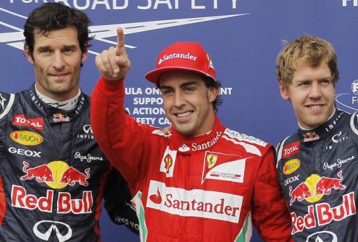 El piloto Fernando Alonso (c), junto a Mark Webber (i) y Sebastian Vettel (d) al finalizar las sesiones de clasificación del Gran Premio de Alemania.
