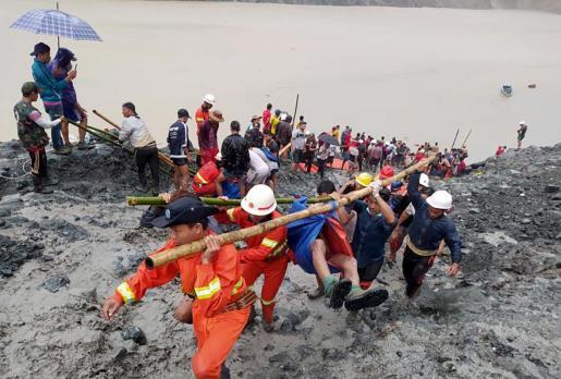 Los trabajadores de rescate llevando el cuerpo de una víctima después de un accidente de deslizamiento de tierra en un sitio de minería de jade en Hpakant,