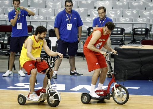 Sergio Llull y Rudy Fernandez juegan con dos triciclos eléctricos tras el entrenemiento realizado hoy en Barcelona.