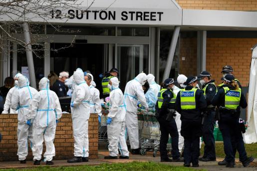 Bomberos de Melbourne equipados para protegerse del coronavirus reparten víveres en un edificio con contagiodos de la COVID-19.