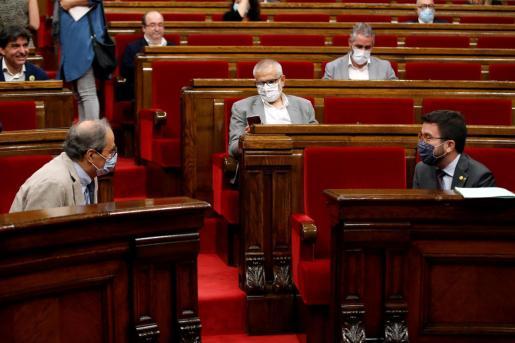 El presidente de la Generalitat, Quim Torra, conversa con su vicepresidente, Pere Aragonés (d), en el hemiciclo del Parlament donde se celebra un debate monográfico sobre la situación de las residencias de ancianos, tras registrar elevadas cifras de contagios y mortalidad por la COVID-19.