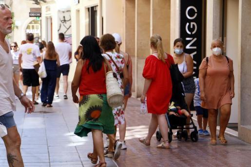 Gente con mascarillas y sin en el centro Palma.