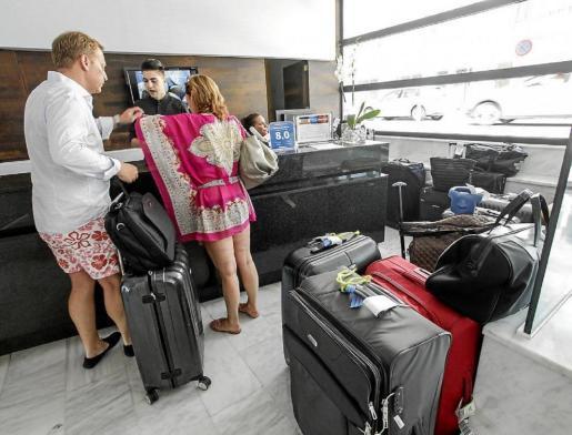 Dos turistas extranjeros en la recepción de un hotel en Mallorca.