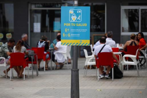 Un cartel informa de la obligatoriedad de usar mascarilla en una calle en L'Hospitalet, este domingo.