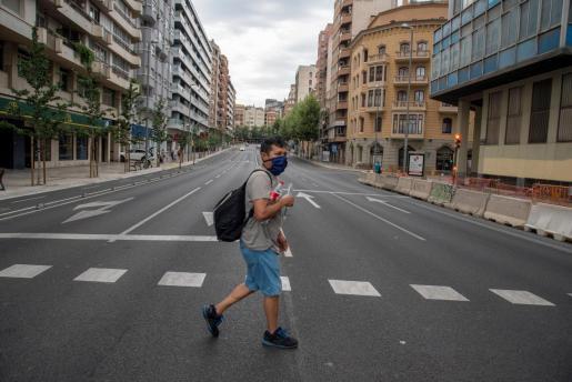 Un vecino cruza la calle en una avenida de Catalunya prácticamente vacía.