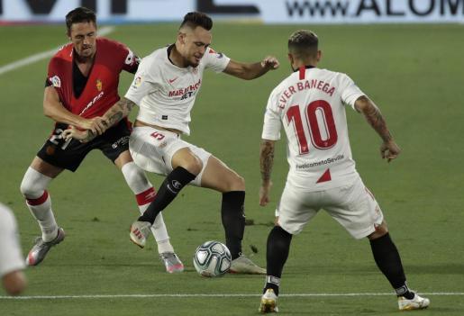 El delantero argentino del Sevilla FC Lucas Ocampos (c) lucha con Antonio Raíllo, del RCD Mallorca (i).