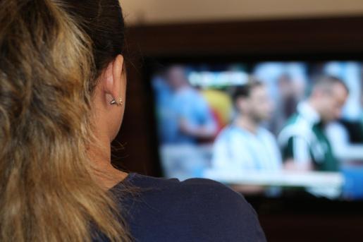 Una mujer viendo un partido de fútbol en televisión.