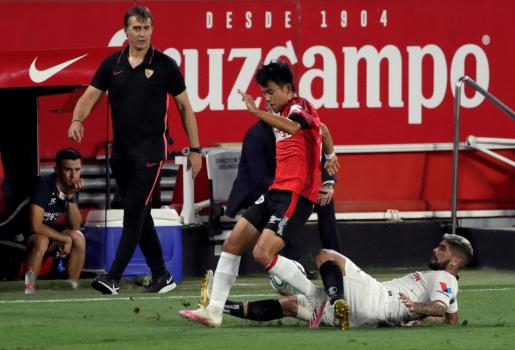 El centrocampista del Mallorca Takefusa Kubo (c) trata de superar la entrada de Éver Banega, del Sevilla.