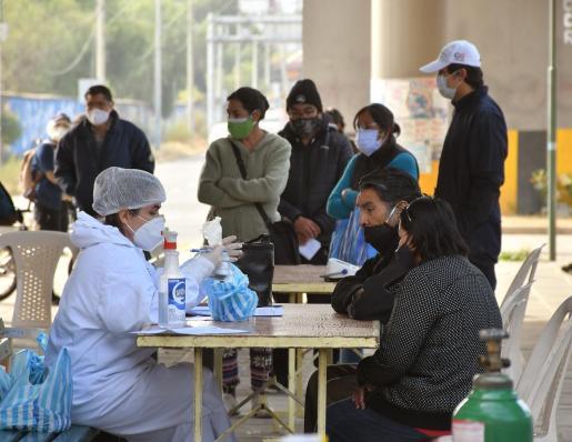 Un integrante del personal sanitario atiende a personas que acuden a realizarse pruebas de detección de COVID-19 en un puesto de atención médica instalado en plena calle bajo un puente, este martes en Cochabamba (Bolivia).