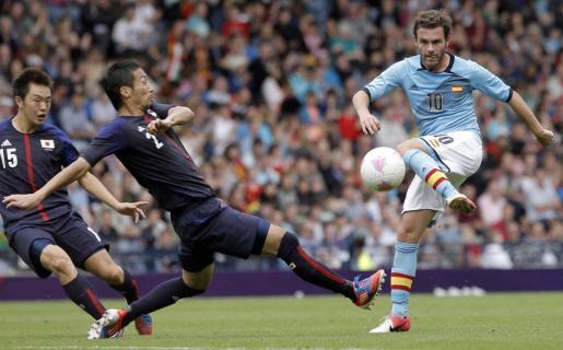El delantero español Juan Mata (d) disputa un balón a los japoneses Tokunaga (c) y Saito, durante el partido correspondiente a la primera fase de los Juegos Olímpicos de Londres.