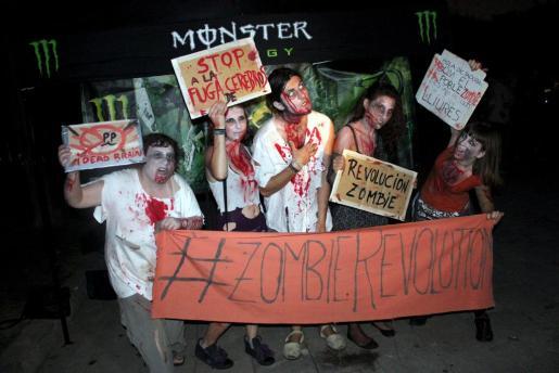 Jóvenes disfrazados de zombies, con la habitual indumentaria desgarrada y repleta de sangre, sujetan carteles y pancartas.