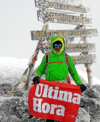 Carlos Prieto, con la bandera de UH, en Uruhu peak, el techo de África.