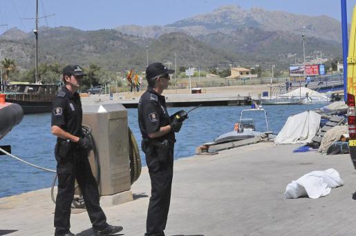 Dos agentes de la Policía Local de Andratx, junto al cuerpo sin vida del submarinista, en el Port d'Andratx.