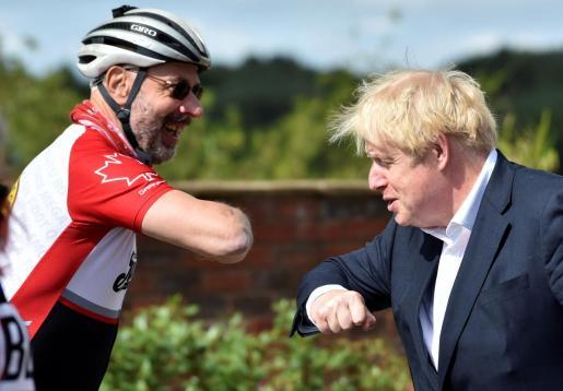 Boris Johnson saluda al ciclista Robert Cleave, durante un acto oficial.
