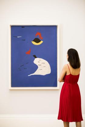 Una mujer observando la obra Peinture (Femme au chapeau rouge).