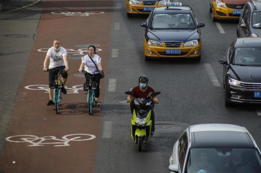 Ciudadanos, en bicicleta por las calles de Beijing.