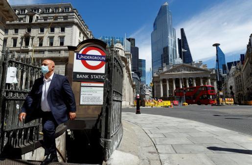 Un hombre sale de una boca de metro en Londres.