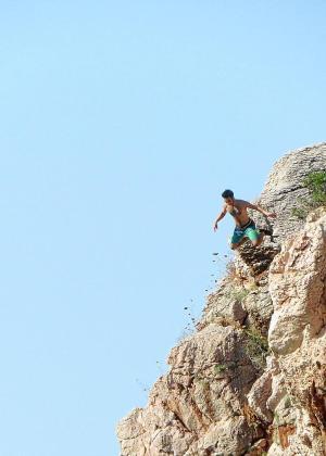 Un joven saltando desde las rocas en Cala Deià.