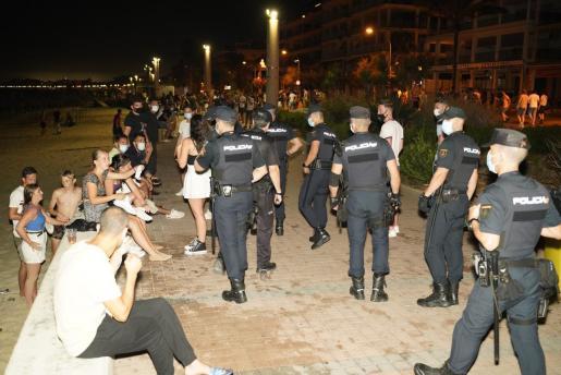 Un gran número de agentes de la Policía Nacional camina por el paseo de la Playa de Palma el pasado viernes por la noche. JOSÉ DE ORBE