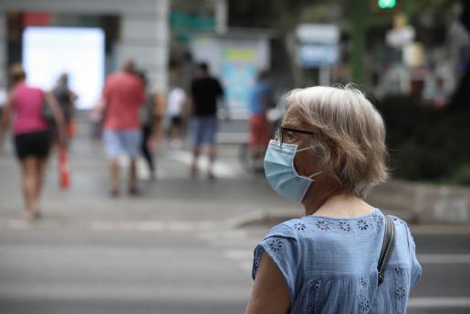 Una mujer, en la calle haciendo uso de la mascarilla.