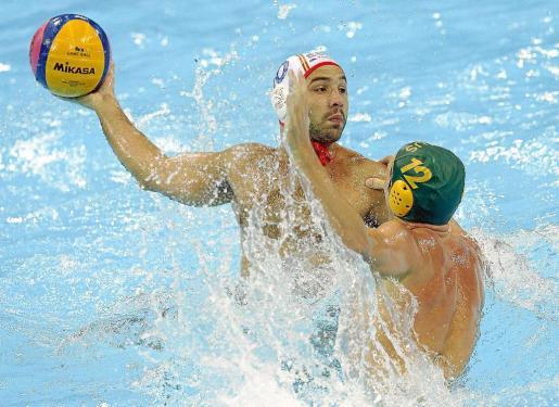 El jugador de la selección española Felipe Perrone (i) pelea por el balón con el australiano Billy Miller, durante su partido de la fase grupos del torneo olímpico de waterpolo.