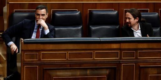El presidente del Gobierno, (i) y el vicepresidente segundo y ministro de Derechos Sociales, en una imagen de archivo en los escaños del Congreso.