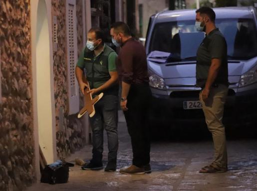 Tres guardias civiles observan un crucifijo junto al domicilio de la pareja.