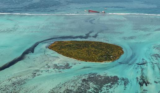 Una fotografía aérea muestra el MV Wakashio, un buque granelero de bandera panameña de propiedad japonesa (arriba) con fugas de petróleo cuando encalló en la costa sureste de Mauricio.