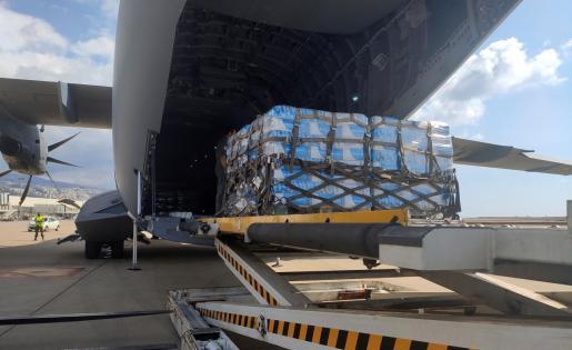 Operarios descargan sacos de harina de trigo del avión del Ejército del Aire español, que ha aterrizado este martes en una base aérea militar en Beirut.