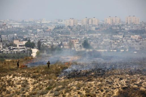 Soldados israelíes sofocan un conato en una zona de matorral cerca de la frontera con Gaza, donde los globos incendiarios han causado estragos en las últimas jornadas.