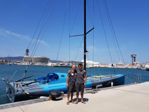 Josep Costa (mánager) y Dídac, ante el barco que participará en la regata, pintado con el apoyo de Álex.