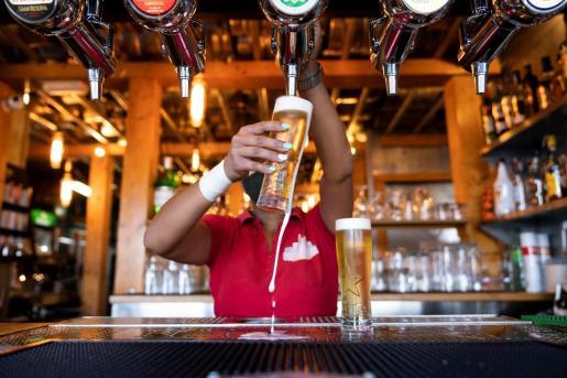 Una camarera sirve unas cervezas en un bar de Santa Cruz de Tenerife.