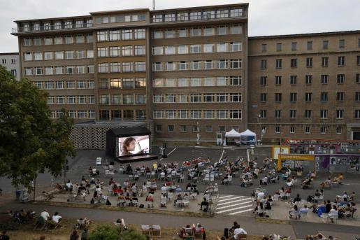 La gente disfruta de una película en el cine al aire libre en el patio del Museo de la Stasi en Berlín.