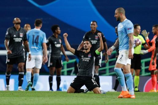 El jugador del Olympique de Lyon Houssem Aouar celebra la victoria de su equipo ante la desolación de los jugadores del Manchester City en los cuartos de final de la Liga de Campeones en Lisboa.
