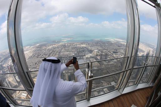 Varias personas toman fotos del paisaje desde la nueva sala de estar más alta del mundo, situada en la torre Burj Khalifa de Dubai (Emiratos Árabes Unidos), que fue inaugurada el pasado año.