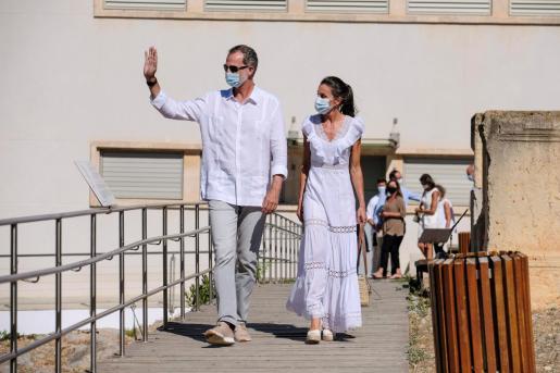 El rey Felipe VI (i) y la reina Letizia saludan durante su visita a Ibiza.